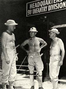 "3 shirtless men in khaki pants and boots talk outside a building with a sign ""Headquarters 91st Infantry Division"""