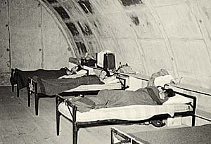 3 men, each lies on a cot, inside a cement igloo.