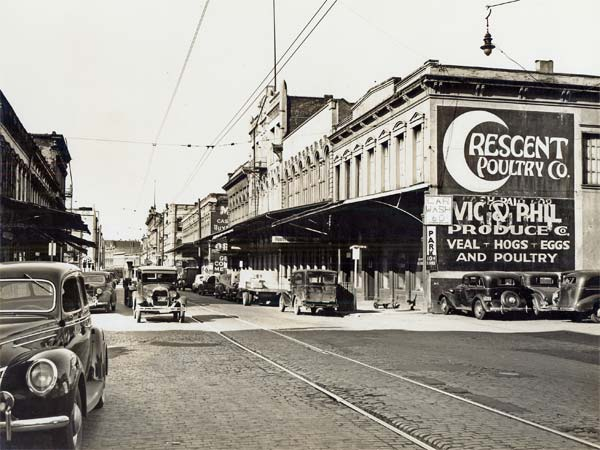 Astreet at Front & Alder in 1941 with cars of the time, street car tracks & buildings with signs advertising poultry & produce.