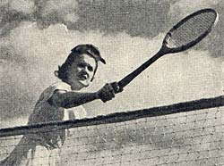 Photo of woman holding tennis racket over tennis net on bright day with few clouds in the sky.