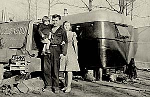 Photo of man holding young child with his wife standing next to him. They stand outside a trailer in a trailer park.