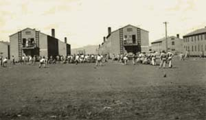 Barracks at Camp White near Medford in 1943 show men recreating outside in the dirt yard by large buildings.