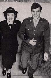 Woman & man, both in military attire, walk up a stairway.