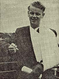 Photo of Ivan Jacobsen with left arm in a sling. He holds a cigarette in the right hand.