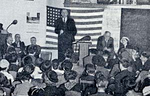 Photo of man on stage by podium in front of American flag talking to a group of dozens of people.