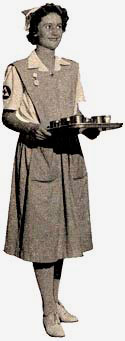 Woman dressed in nurse's aide uniform holding a tray with dishware.