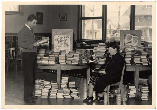 A man stands, a woman sits. Two tables are stacked high with books as well as stack of books on the ground.