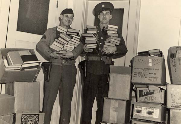 2 men hold stacks of books and are surrounded by boxes of books stacked high.