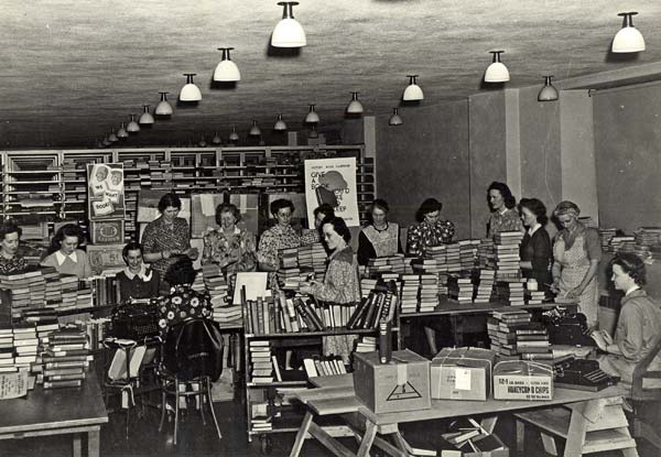 Photo of women in a large room filled with tables stacked high with books.