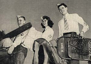 Photo of 3 teenagers (girl and 2 boys) carrying salvage material like metal chairs and newspapers.