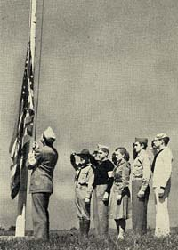 A man in uniform raises an American flag on a pole on a grassy lawn while 5 youths stand at attention.