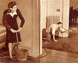Photo of woman with bucket and pump handle on one side of living room wall. Man holding hose toward something in the other room.