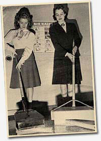 Photo of 2 women showing things that look like brooms or scoops with long handles.