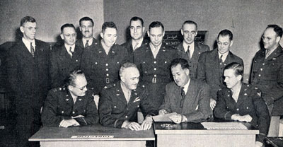 9 men standing, 4 men sitting at a desk examining a document. All dressed in officer's uniforms.