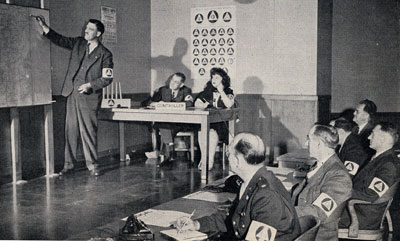 Man stands at front of classroom pointing to something on a map. Class of men and 1 woman look on.