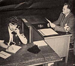 Woman sits at a desk talking on the phone and writing on a paper. Man sits at desk next to her looking at document.