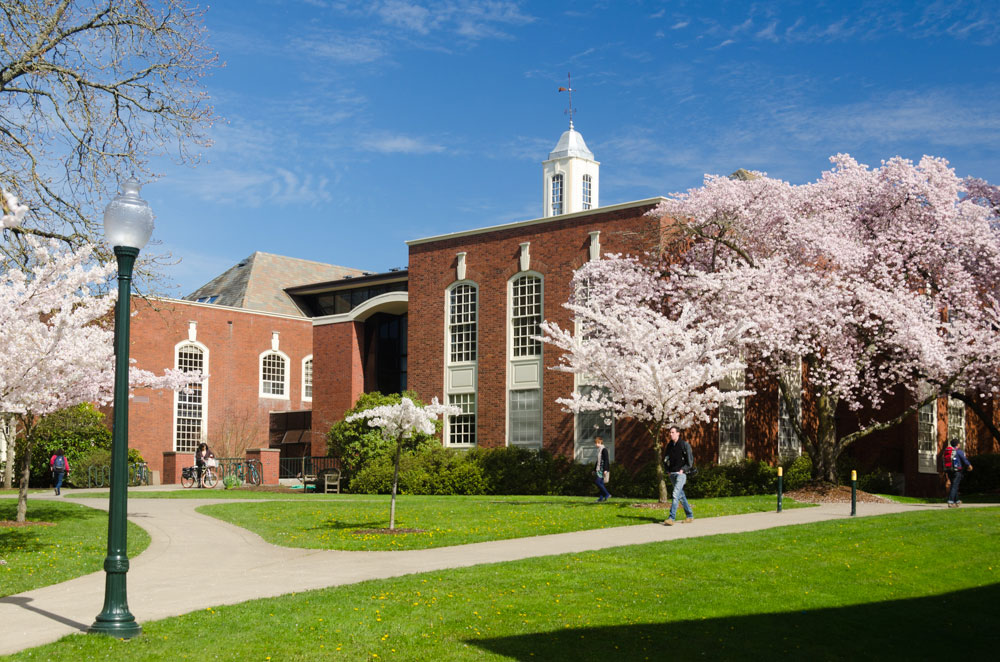 Photo of Building on Willamette University campus with cherry trees in bloom in front.