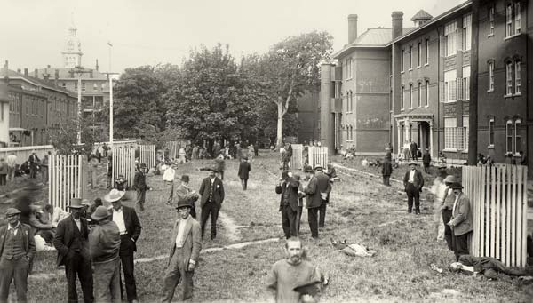 Photo of dozens of men standing around in a yard outside the Oregon State Asylum building.
