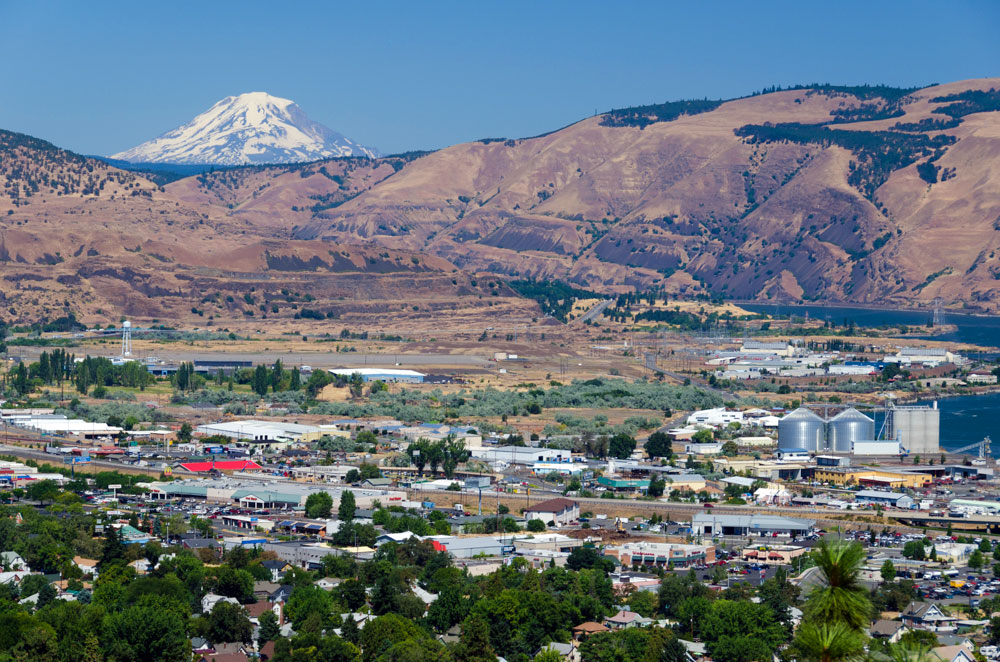 View of city of The Dalles with mountains in the background.