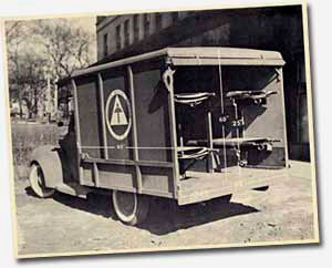 Ambulance from 1939 with back door open to show room for stretchers inside.