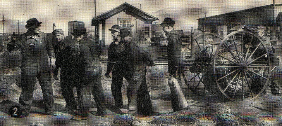 8 men in overalls and hats work with railroad equipment in a rail yard