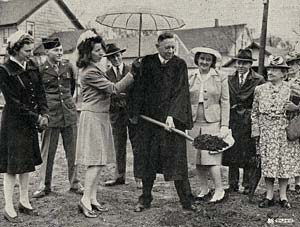 Photo of minister with shovel pulling dirt out of ground. A woman holds an umbrella over him and 6 others stand to watch.