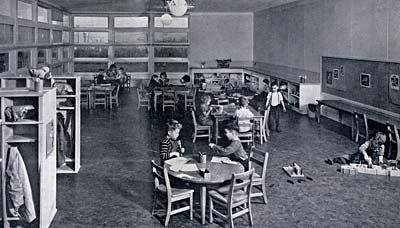 Photo of a classroom with desks, chairs and places to hang coats or store toys. A few children sit at tables or play on floor.