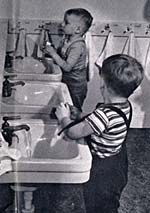 2 small boys at child size sinks in a bathroom wash their hands.
