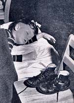 Photo of younb boy napping on a bed. His shoes are on a chair to the side.