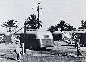 2 women hang up laundry outside a mobile home. There are palm trees in the background so the location probably isn't Oregon.