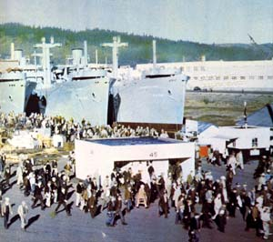 Photo of hundreds of people walking around a shipyard in Portland. 3 naval ships show in the background.