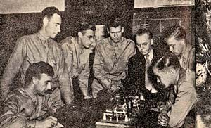 7 men gather around a table to learn military training.