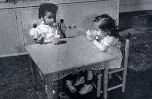 2 small girls sit at a child size table with cups of something.