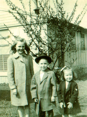 3 children stand in front of a house wearing coats.
