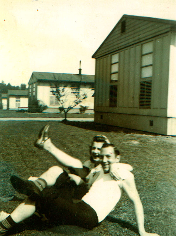 Man & woman sitting on a lawn in front of a home looking happy.
