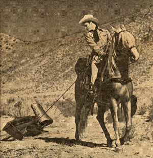 Photo of Roy Rogers on horse dragging scrap metal by a rope behind him.