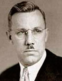 Photo of Conde McCullough wearing suit, tie and glasses.