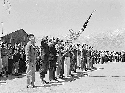 Japanese men and women lined up outside buildings with American flag.