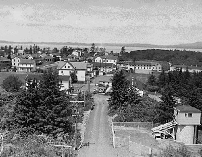 Typical looking community of 1942 with buildings, dirt roads and trees to the side. The ocean in the distance.