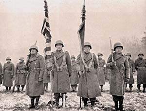 Men in military coats with helmets stand in lines. Front line holds flags. Looks like snow on ground.