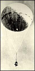 Photograph of balloon with bomb floating through air.
