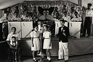 Band sits behind 2 girls singing along with 3 men and a boy. All are dressed in white with ties.
