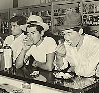 Three Japanese men at a counter in a drug store eating & drinking.