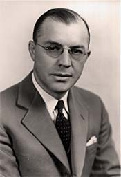 Photo of Milton Eisenhower in suit and tie, wearing glasses.