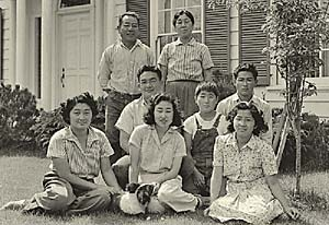 Family of 8 pose before their typical American house.