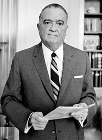 Photo of J. Edgar Hoover in suit and tie holding papers and looking at camera.