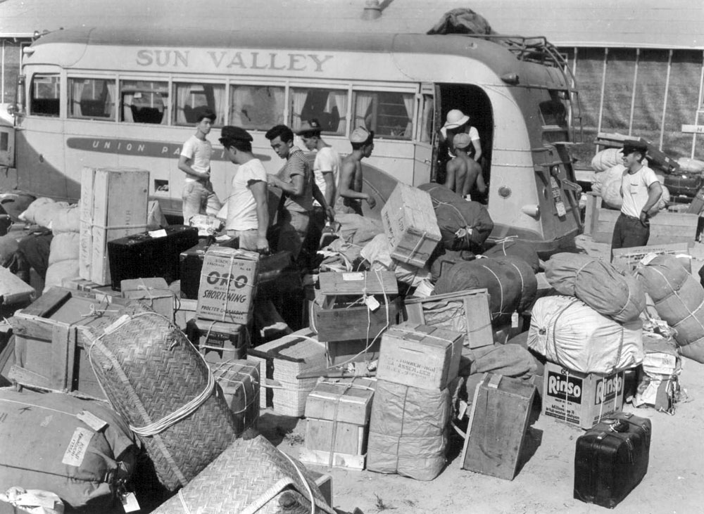 "A bus with ""Sun Valley"" printed on side sits with piles of luggage in front & people trying to sort it."