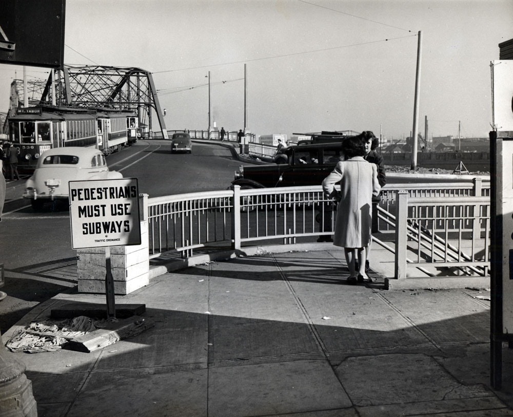 2 ladies stand on the sidewalk looking out at the Morrison Bridge. Cars from the 1940s drive by and a trolley car on a track.