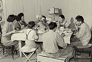 Family of 7 seated around a table eating.
