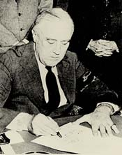 Rossevelt sitting at a desk signing a piece of paper.